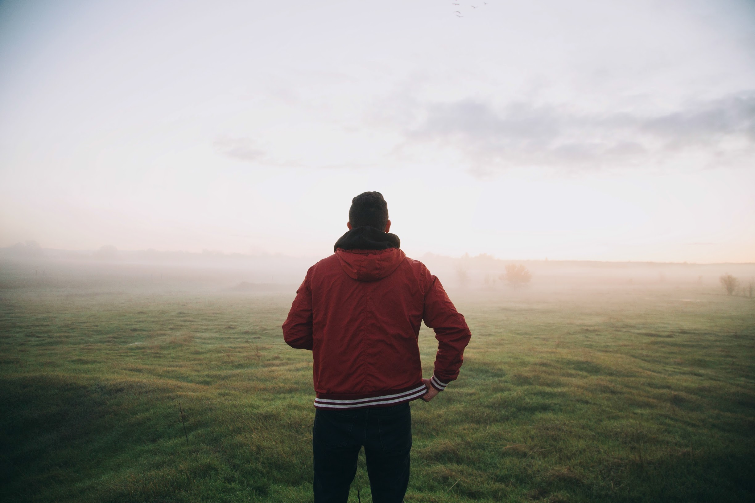 man-in-red-jacket-looking-at-cloud-cover